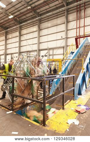 A roll cage of cardboard is emptied into recycling machinery