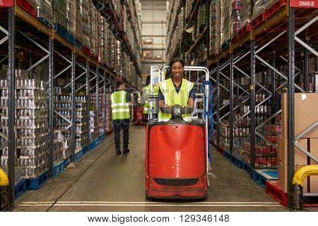 Woman operating tow tractor in a busy distribution warehouse