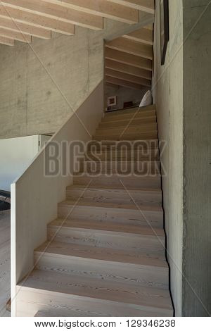 Interior of a modern chalet in cement, wooden staircase
