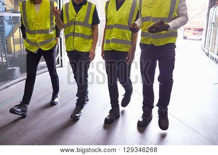 Four colleagues walk in an industrial interior, low section