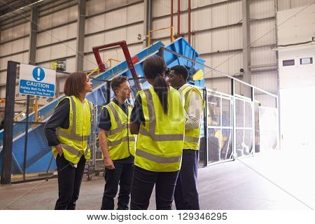Four coworkers in discussion in an industrial interior
