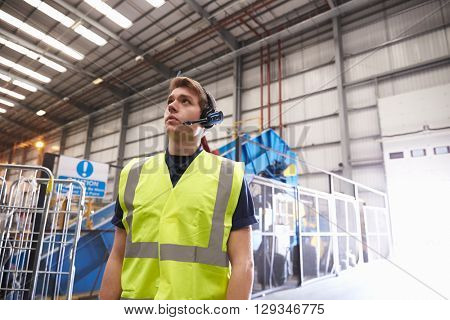 Man with reflective vest and headset standing in a warehouse