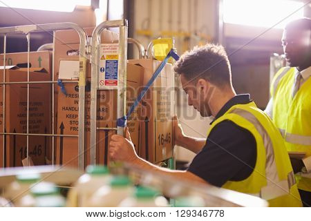 Man preparing roll cages for delivery, watched by supervisor