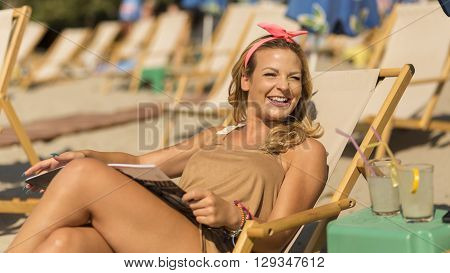 Attractive blond lying on a sunbed on a beach reading a magazine and enjoying the sun