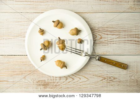 Acorns on a plate and fork on the table