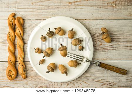 Acorns on a plate fork and bread on the table