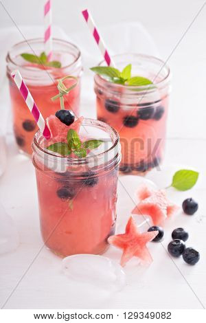 Watermelon lemonade in mason jars with blueberry
