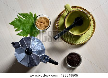 Cup and spoon with cane sugar, coffee powder, coffee machine and green leaf