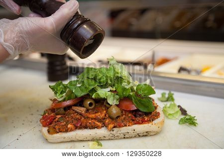 Close up of a person hands preparing chicken, lettuce and tomato sandwich in a cafeteria