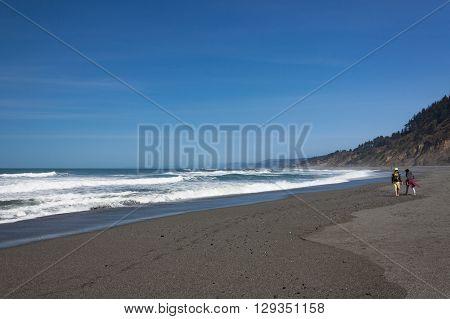 Young couple walking along wave-swept California beach