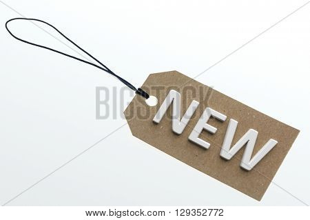NEW word on cardboard tag on white background.Isolated
