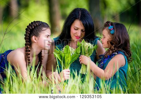 Beautiful Young Woman with Two Children in the park. happy family outdoors. woman and two children having fun in summer. Mother and daughters in the park. Happy parent and Kids.