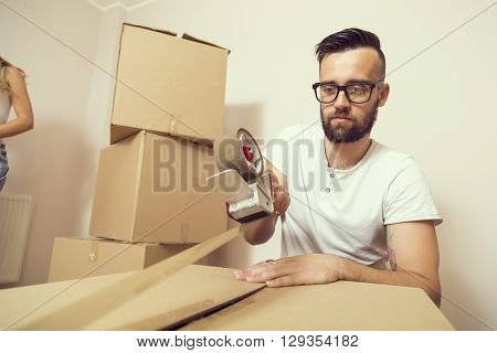 Young man packing things and taping boxes preparing for moving out the appartment