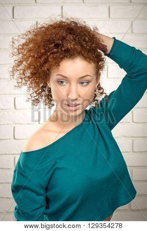 Beautiful ginger woman correcting her hair portrait
