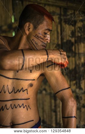 SANTO DOMINGO ECUADOR - JANUARY 26 2015: Indian man Colorados (Los Tsáchila) tribe in national clothes paints hair juice plants achiote for ritual purposes on January 26 2015 in Santo Domingo Los Rios Ecuador