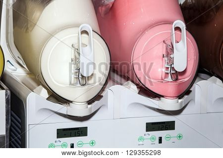 Two moist juice machines in action. Machine for making ice slushy drinks