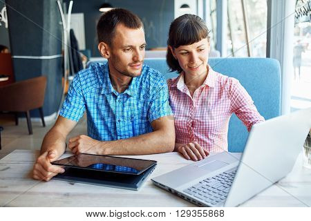 young man and woman with laptop typing on the keyboard in cafe. palm, tablet PC and laptop closeup ** Note: Visible grain at 100%, best at smaller sizes