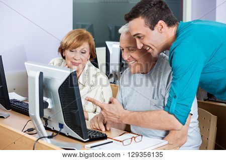 Tutor Assisting Senior Students In Using Computer At Class