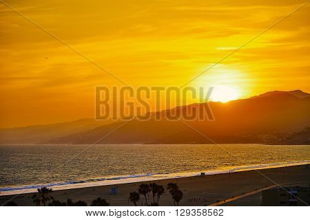 Sunset at Santa Monica Beach. The sun sets behind the hills
