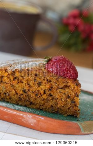 Macro shot of a slice of carrot cake with a strawberry on top cofee in brown ceramic mug red flowers at the background