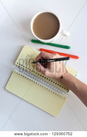 A woman hand holding a black pen and writing 2016 on a yellow notebook. Overhead shot of coffee red pen orange pen writing hand