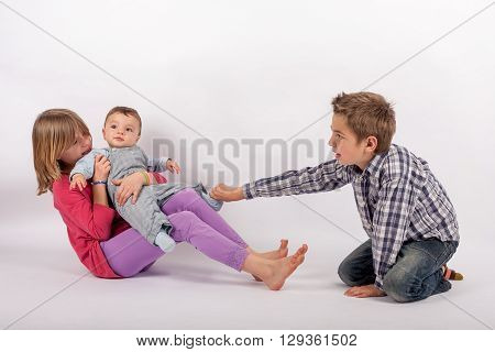 Siblings arguing over their small brother - the girl and the boy sibling also wants to play with the cute baby brother.