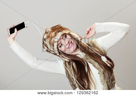 Winter girl listening music using phone with headphones strechting. Happy woman wearing fur vest and warm hat in freezing cold time having fun posing.