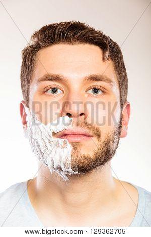 Man With Shaving Cream Foam On Half Of Face.
