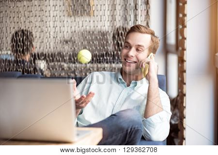 Nice to hear you. Cheerful delighted handsome man sitting at the table and holding tennis ball while talking on cell phone