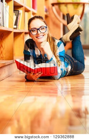 Education school concept. Casual female student fashionable girl in blue glasses lying on floor in college library with book reading. Indoor