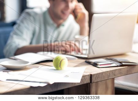 Working atmosphere. Selective focus of tennis ball lying on the table while pleasant handsome delighted man talking on cell phone in the background and using laptop