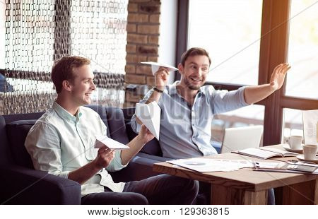 Joyful mood. Positive delighted joyful smiling colleagues sitting at the table and playing with paper planes while having fun