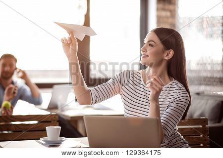 Have some fun.  Positive content charming  sitting at the table and playing with paper plane while her colleague talking on cell phone in the background