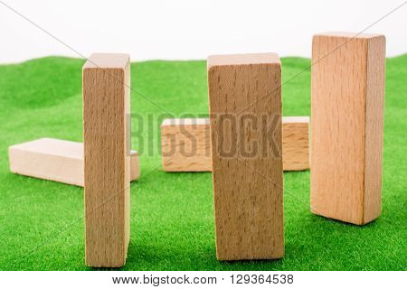 Wooden domino pieces on a fake green grass