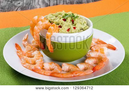 prawns on a white plate with guacamole sauce in a bowl on an old rustic table close-up
