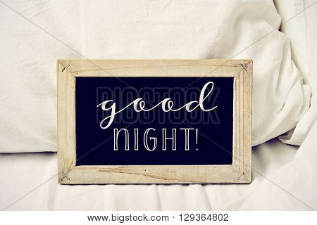 closeup of a wooden-framed chalkboard with the text good night written in it, placed on a comfortable bed