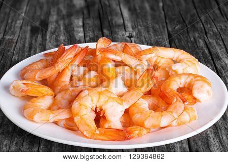 boiled tails of shrimps on a white plate on an old rustic table close-up studio lights