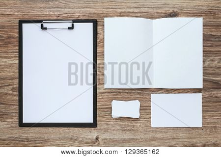 Corporate identity template set on wooden desk. Business stationery mock-up with envelope, card, etc. Top view.