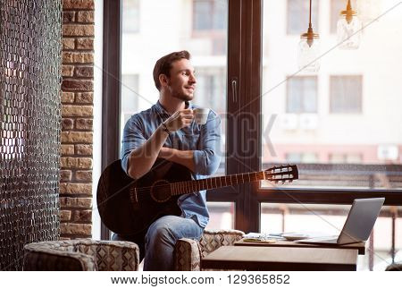 Reach the harmony with mind. Pleasant delighted handsome smiling man holding the guitar and leaning on the armchair while enjoying coffee