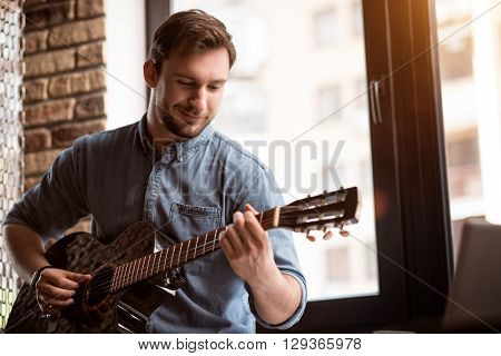Feel the music. Positive handsome delighted man smiling and playing the guitar while expressing gladness