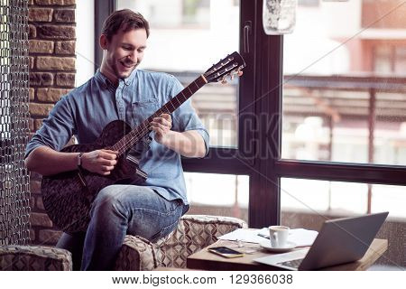 Joyful mood. Cheerful handsome smiling leaning on the armchair and playing the guitar while resting