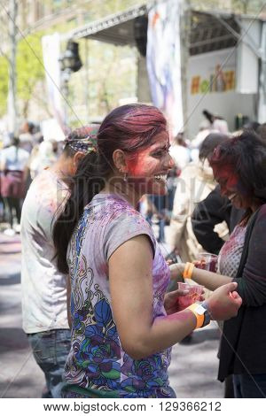 NEW YORK - APR 30 2016: A woman in the crowd with colorful powder on her face celebrating the Holi Hai Festival of Colors hosted by NYC Bhangra in New York on April 30 2016.