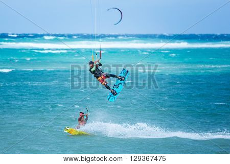 Boracay island, Philippines - January 25: two kiteboarders using rope tow while riding, one of them performing jump