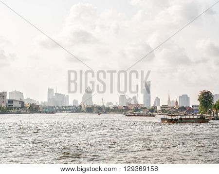 Passenger boat on Chaopraya river and city scape in Bangkok