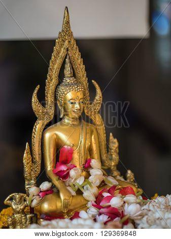 Buddha statue with sacred lei flower garland
