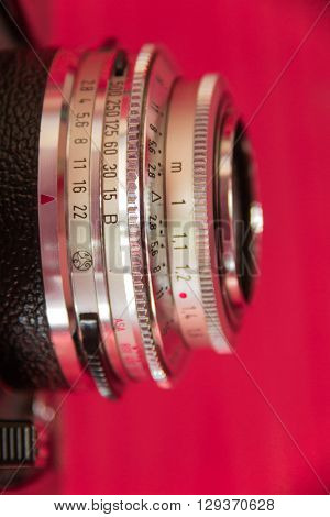 close up of rangefinder camera lens with crimson background