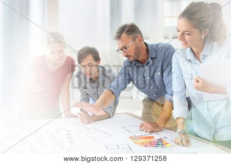 Students with teacher working on project around table