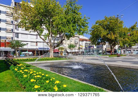 Vila Nova de Famalicao, Portugal.?? September 06, 2015: Fountain in the Dona Maria II Square in Vila Nova de Famalicao. Shopping Town entrance in the tall building. Braga, Portugal.
