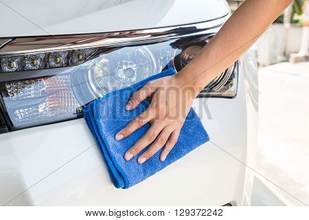 Hand with blue microfiber cloth cleaning white car.