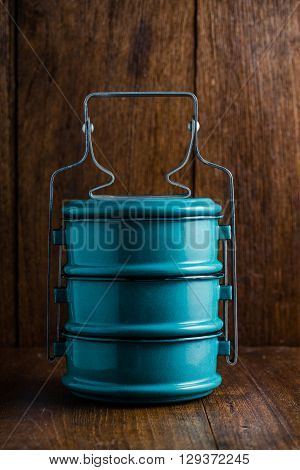 Metal tiffin Thai food carrier on wooden background.